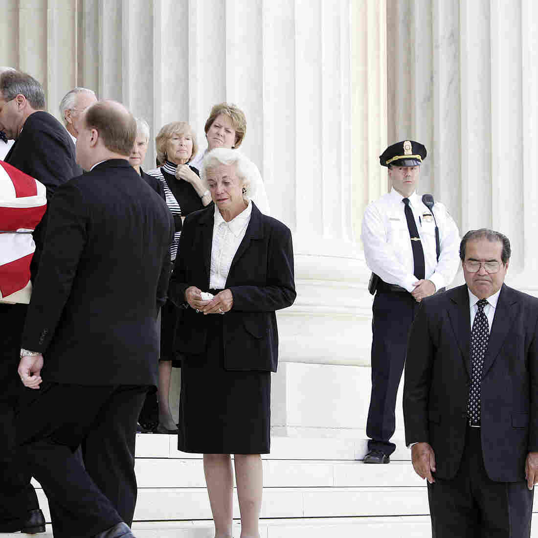 U.S. Supreme Court Associate Justices Sandra Day O'Connor, center, and Antonin Scalia, right, watch as pallbearers carry the casket of Chief Justice William Rehnquest into the Supreme Court where he will laid in repose in September 2005.