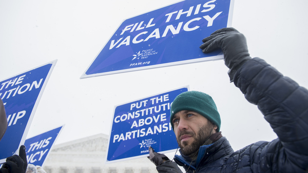Activists with People For the American Way demonstrate outside the Supreme Court on Monday, calling on Congress to give consideration to whomever President Obama nominates to replace Antonin Scalia.