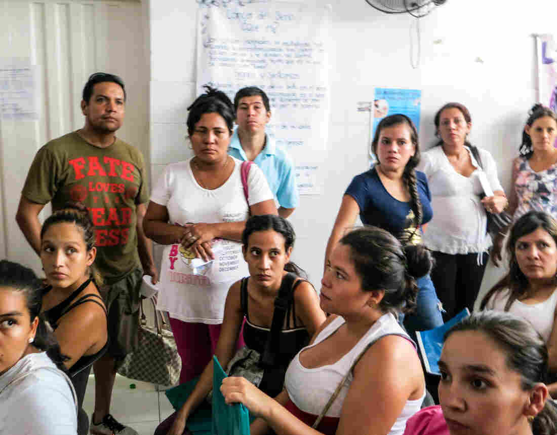 """The man in the T-shirt is Paolo Sandoval, 42. His wife (seated, far right, in a white shirt) is Jessica Vivana Torres, 30. She's 15 weeks pregnant with their first child and came down with Zika three weeks ago. """"I'm really worried about brain damage in the baby,"""" says Sandoval, who listens intently as the ultrasound doctor describes the procedure."""