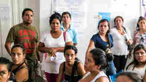 "The man in the T-shirt is Paolo Sandoval, 42. His wife (seated, far right, in a white shirt) is Jessica Vivana Torres, 30. She's 15 weeks pregnant with their first child and came down with Zika three weeks ago. ""I'm really worried about brain damage in the baby,"" says Sandoval, who listens intently as the ultrasound doctor describes the procedure."
