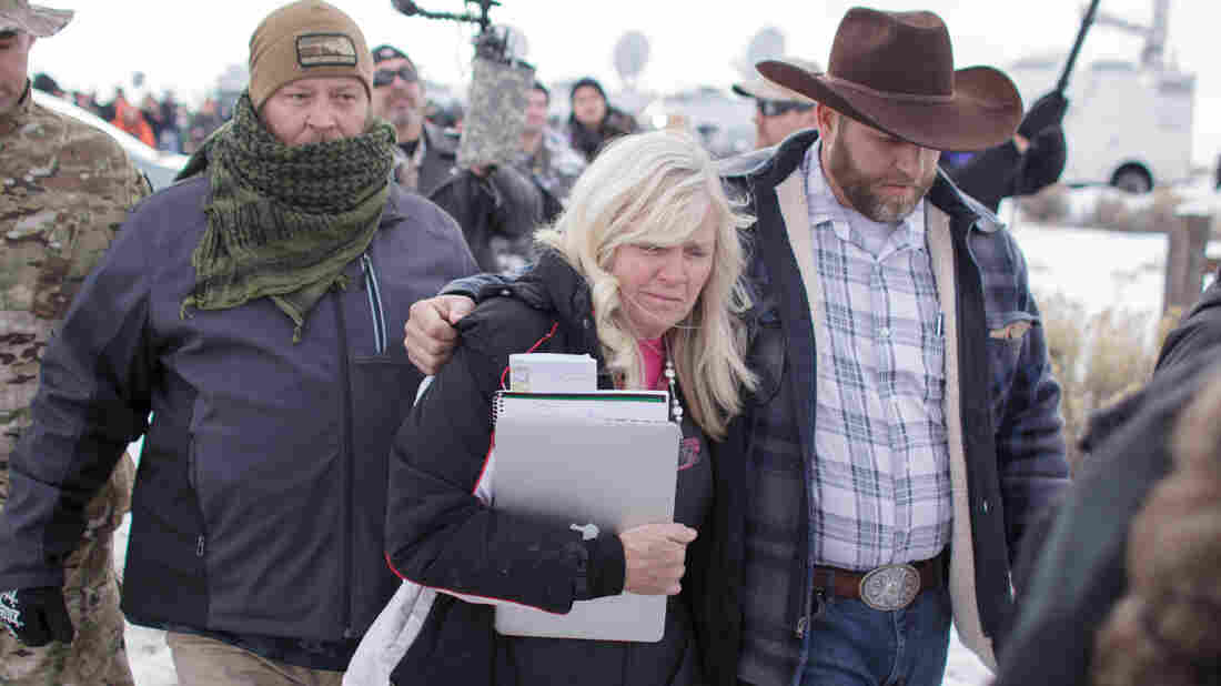 "Shawna Cox, seen here walking with Ammon Bundy and other armed anti-government protesters at the Malheur National Wildlife Refuge near Burns, Ore., last month, cites ""extremely serious public corruption"" in a countersuit. Both Cox and Bundy face federal charges."
