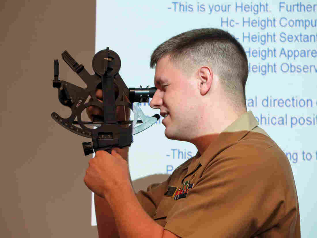 Lt. Daniel Stayton demonstrates how to use a sextant before a class of midshipmen at the U.S. Naval Academy.