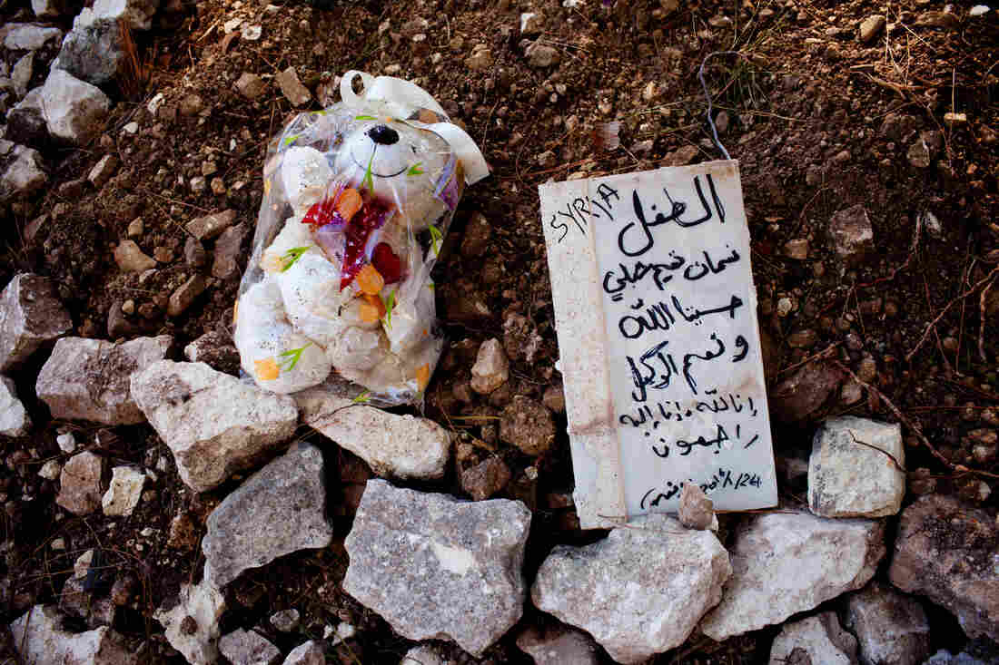 """At a makeshift burial ground in Samos, beyond the edges of a Greek Orthodox cemetery, lie the bodies of three Syrian children. The marker reads, """"The child Noaman Tamim Shibly — For us Allah suffices, and he is the best disposer of affairs. To God we belong, and to him we shall return."""""""