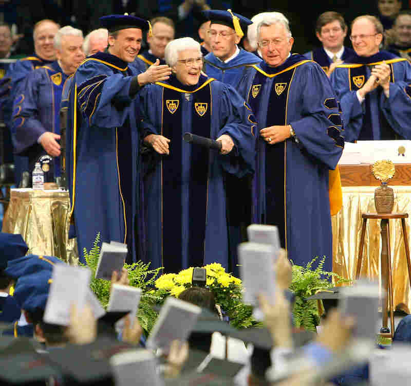 Lee (center) and University of Notre Dame officials look out at the graduates of the class of 2006 as they hold up copies of To Kill a Mockingbird during commencement ceremonies. Notre Dame awarded Lee an honorary degree.