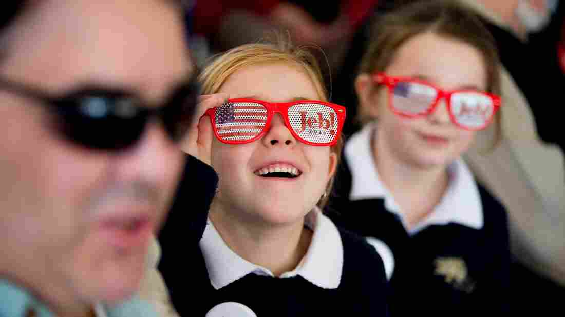 A young girl watches as Republican presidential candidate Jeb Bush arrives to speak at a rally in South Carolina.