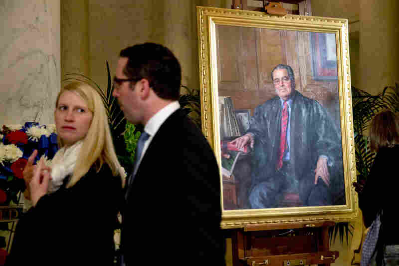 Members of the public walk past a Scalia portrait in the Great Hall of the Supreme Court.
