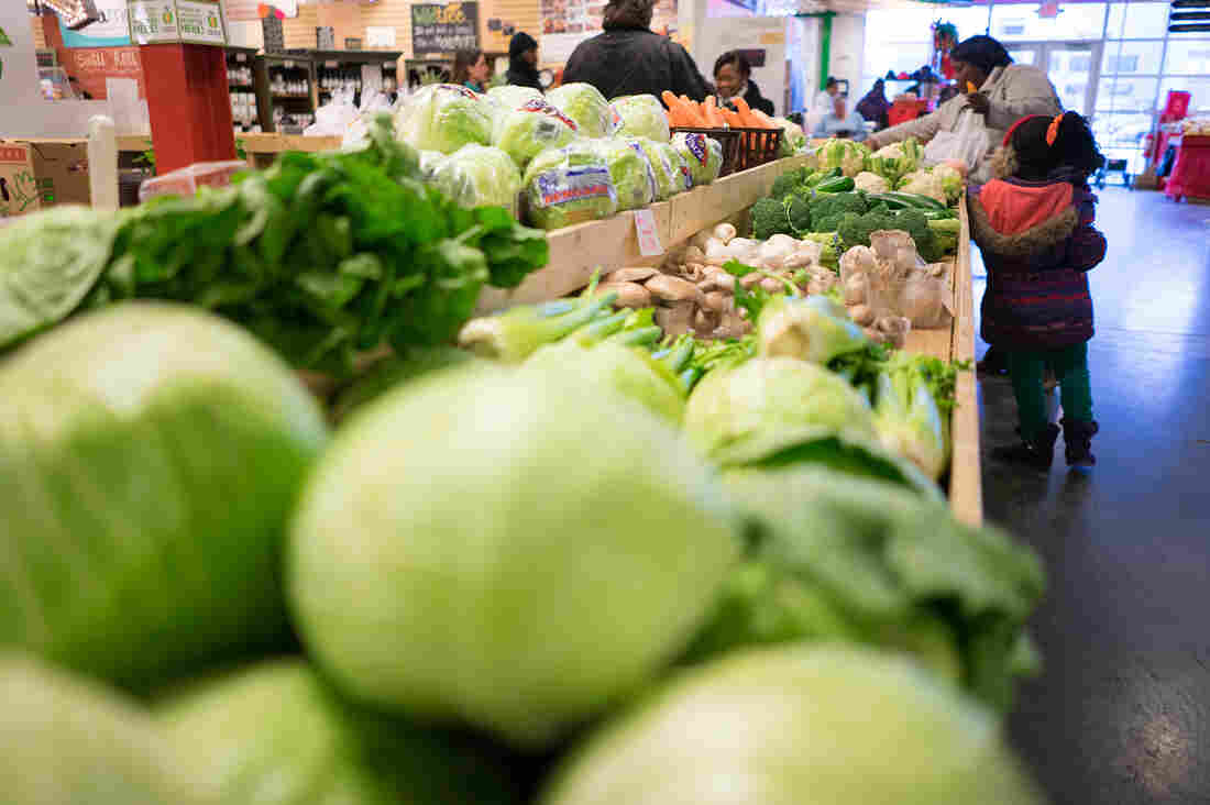 Customers shop for produce at the Flint Farmers' Market this week.