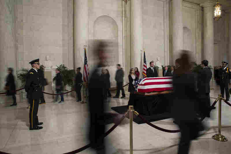 Visitors walk past the casket of Associate Supreme Court Justice Antonin Scalia  as he lies in repose in the Great Hall at the U.S. Supreme Court.