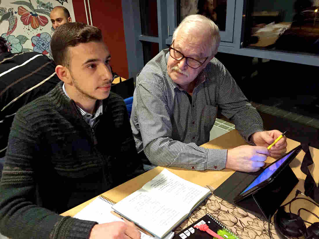 """Kent Norman, a retired Swedish engineer, is helping Syrian teenager Mohamed Obai with language study. """"They're here now,"""" he says, """"so the only thing you can do is to help them."""""""