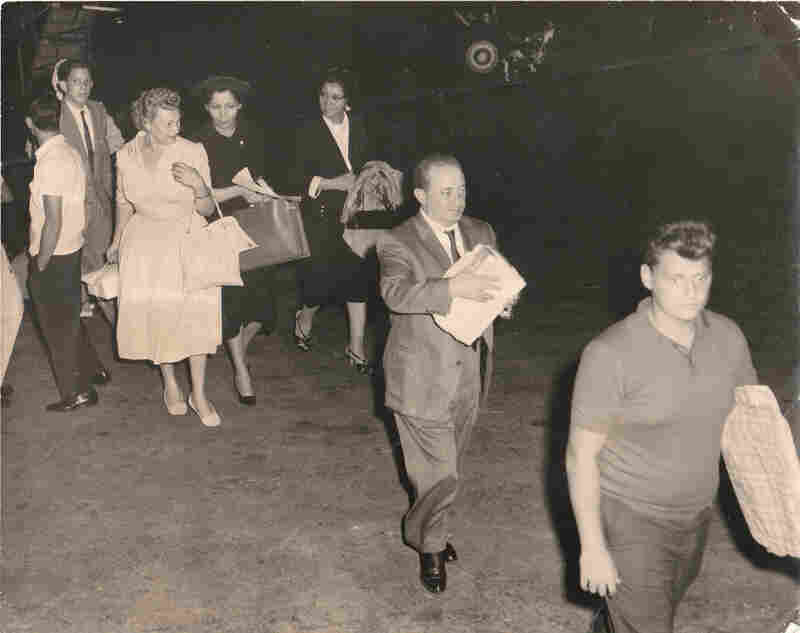 Saul Berenthal (far right) and his father (center) upon arrival in Miami from Cuba in 1960. They are carrying Cuban cigars.