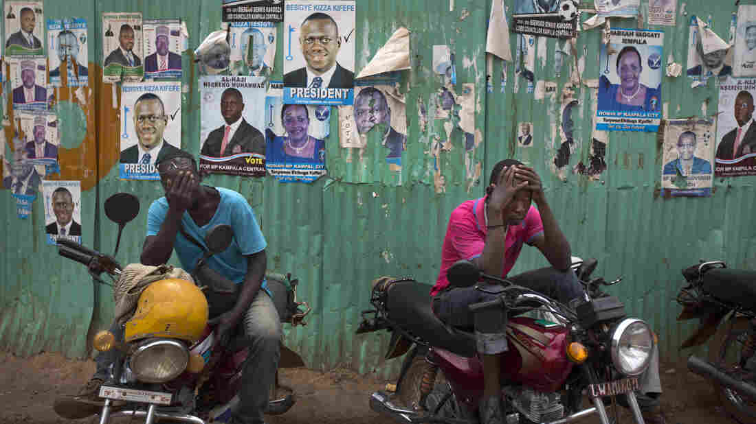 Dejected opposition supporters who work as motorbike taxi drivers hold their heads in their hands shortly after the election result was announced, in downtown Kampala on Saturday.