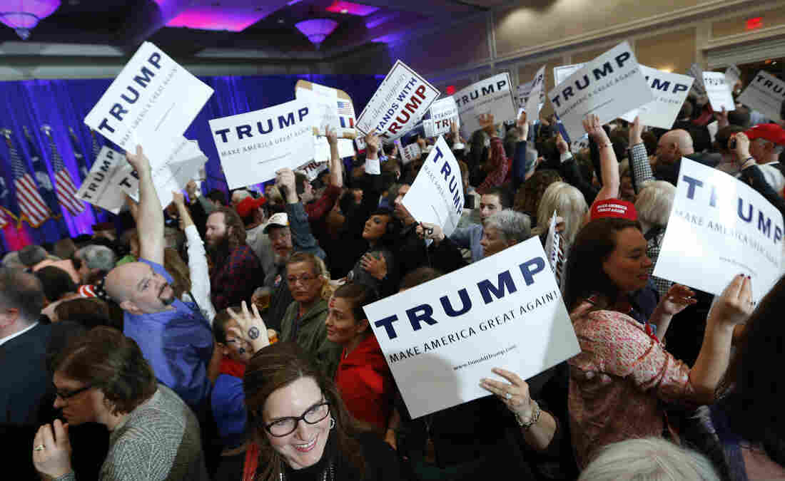 Supporters for Republican presidential candidate Donald Trump hold signs during a South Carolina Republican primary night event in Spartanburg, S.C.