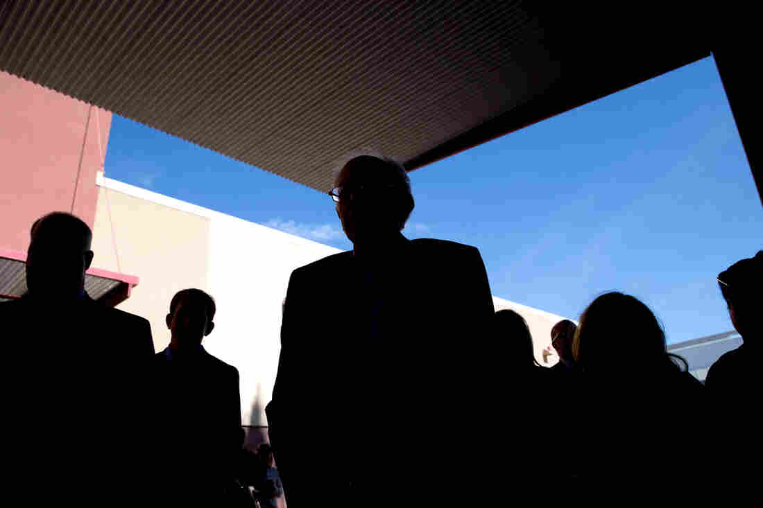 Democratic presidential candidate Sen. Bernie Sanders (center), silhouetted as he talks to voters at a caucus site on Saturday in Las Vegas.