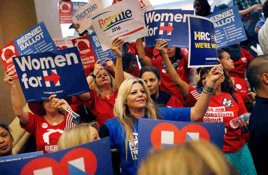Supporters of Hillary Clinton and Bernie Sanders cheer on their presidential candidates before entering a caucus site in Las Vegas.