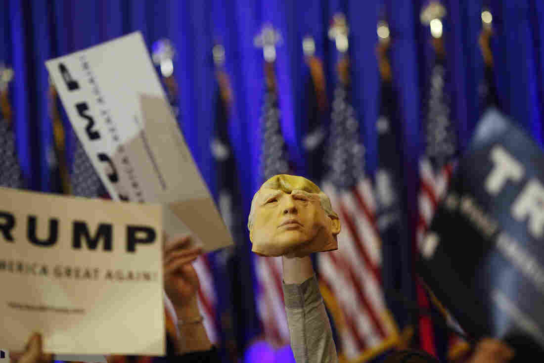 An attendee holds a mask of Donald Trump during a rally in Spartanburg, S.C. Trump won Saturday's South Carolina primary, further entrenching his status as front-runner for the GOP nomination.