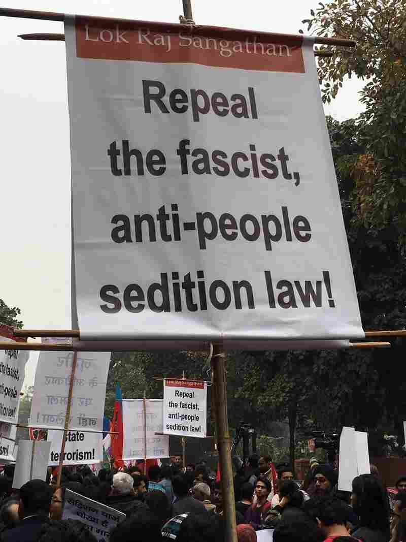 A protester carries a banner calling for a repeal of India's sedition law.
