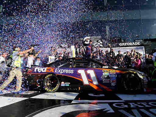 Denny Hamlin celebrates in Victory Lane after winning the NASCAR Sprint Cup Series Daytona 500 at Daytona International Speedway on Sunday.