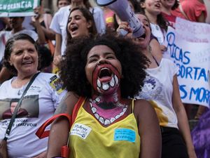 "Countries in Latin America have a range of laws regarding abortion, from completely prohibited to no restrictions. Above: Women in Brazil (at left) demonstrate for abortion rights; a woman in a march in Paraguay (at right) holds a poster reading ""If Abortion is Not Wrong, Then Nothing Is Wrong."""
