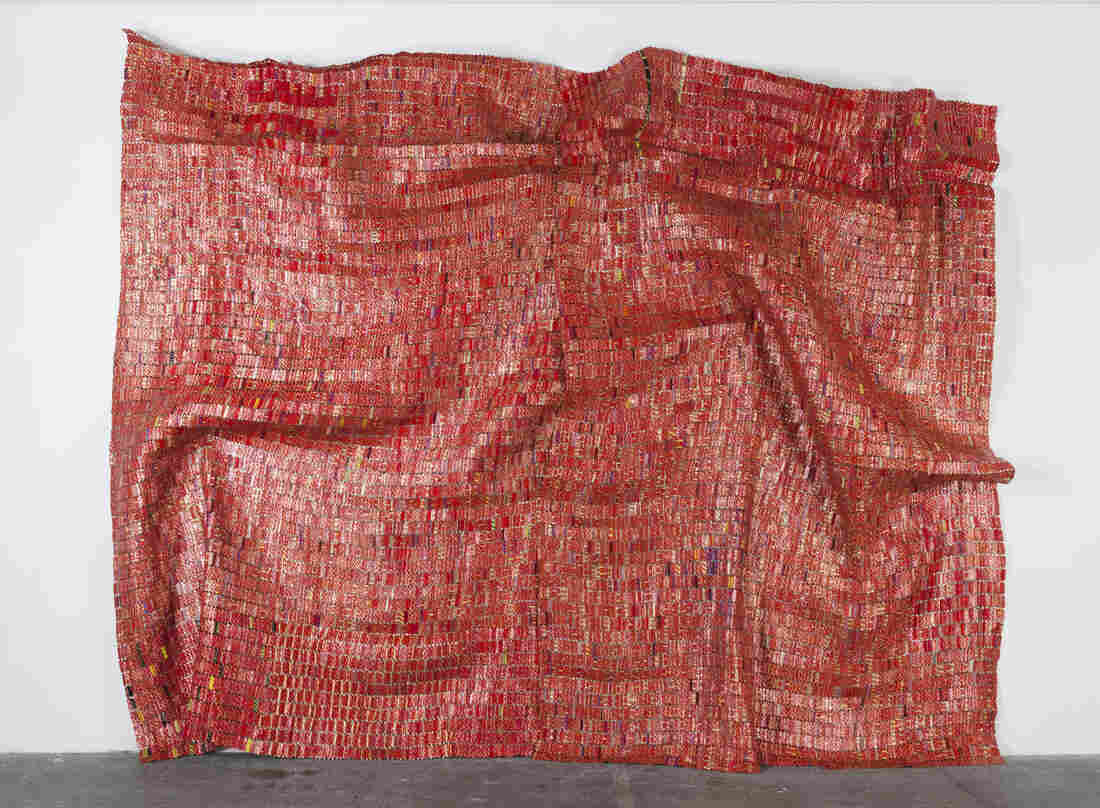 El Anatsui's 2010 Red Block looks like a tapestry, but is actually made of aluminum and copper wire.