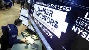 A trader works earlier this month alongside the New York Stock Exchange post where shares of Lumber Liquidators are traded. The company's stock price has been falling ever since a 60 Minutes report on the cancer risk from some of its floor products.