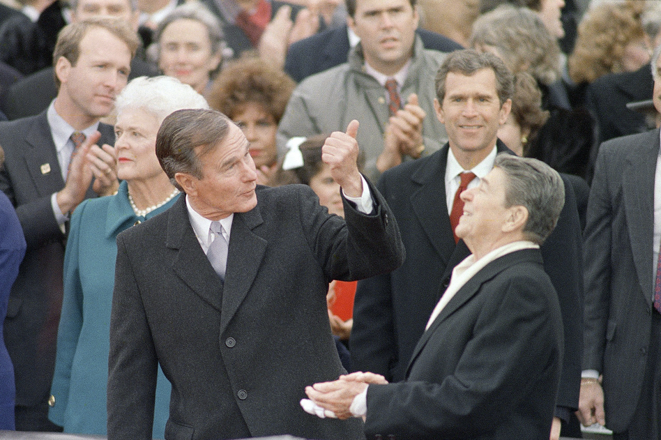George H.W. Bush speaks with President Ronald Reagan, prior to being sworn in as the 41st president of the United States on Jan. 20, 1989. His son George W., later the nation's 43rd president, looks on, with his brother Jeb behind. (Ron Edmonds/AP)