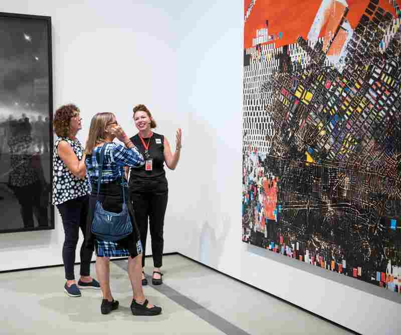 Visitor Services Associate Sacha Baumann talks with two visitors about Mark Bradford's 2006 work Scorched Earth.