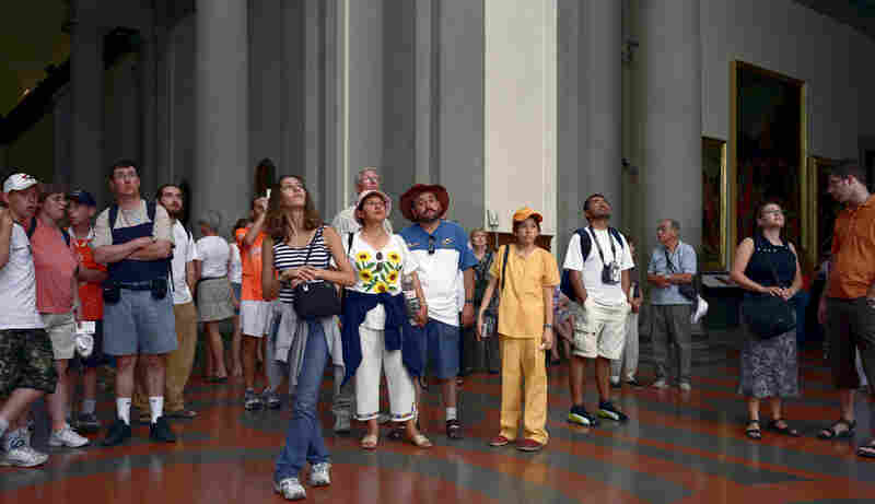 If you look carefully — very carefully — at Thomas Struth's 2004 photograph, Audience 7 (Galleria Dell'Accademia), Florenz, you'll see a man in a hat with sunglasses clipped to the front of his shirt. Click here to see what the reflection in those glasses reveals.