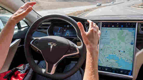 A member of the media tests a Tesla Motors Model S car with an Autopilot system. Regulators and manufacturers are debating whether self-driving cars should have a licensed driver inside as a safety precaution.