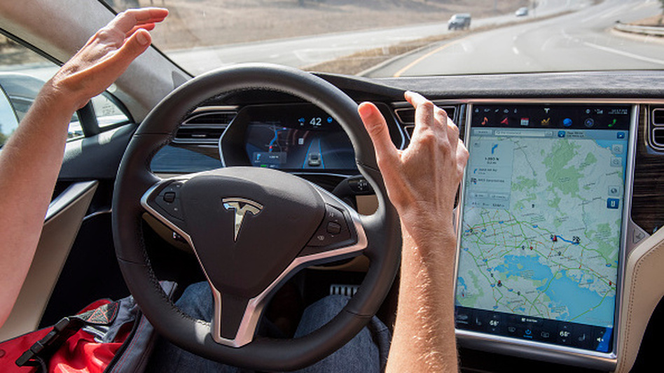 A member of the media tests a Tesla Motors Model S car with an Autopilot system. Regulators and manufacturers are debating whether self-driving cars should have a licensed driver inside as a safety precaution. (Bloomberg/Bloomberg via Getty Images)