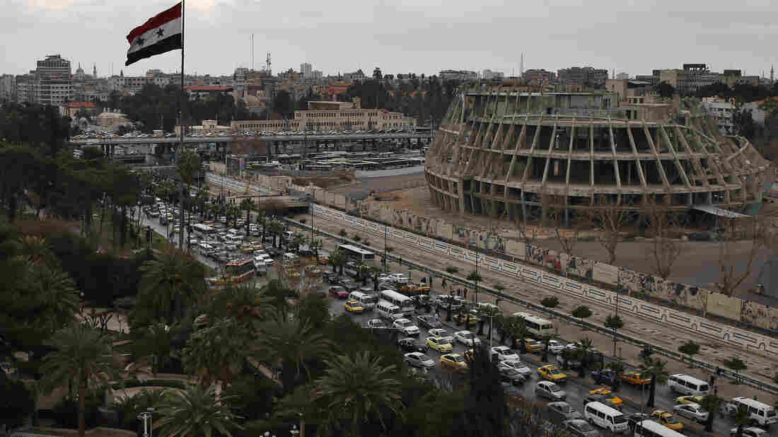 "Syria's regime and opposition groups have agreed on a ""cessation of hostilities."" Here, a Syrian flag waves as vehicles move during rush hour in Damascus on Sunday."