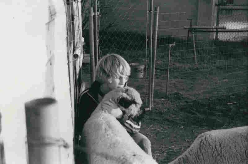 John Putz sits with a sheep.