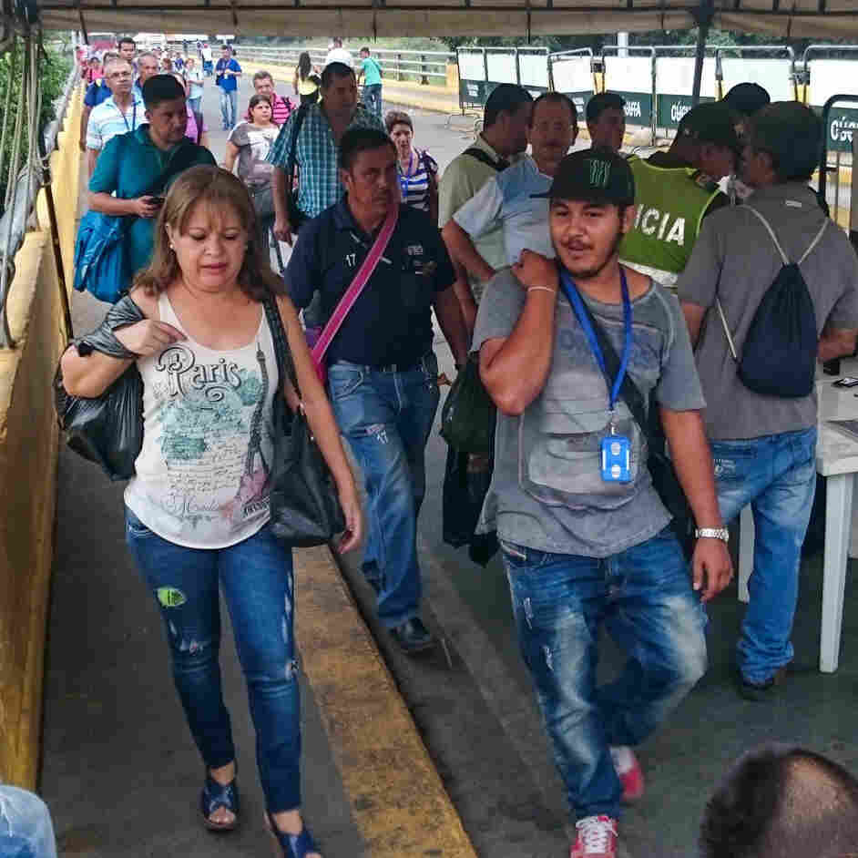 These people have just walked across the bridge from Venezuela to Colombia, where the Colombian immigration authorities are on duty. Many people live on one side and work on the other, crossing so frequently they don't have to register with officials each time.