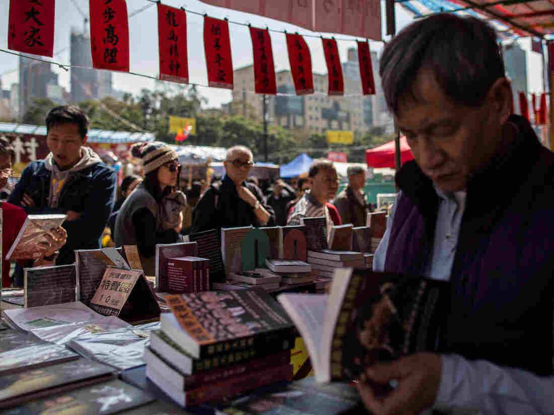 Customers browse books on Chinese politics by Mighty Current, the publisher that has seen five of its booksellers disappear, at a stall set up by political activists in Hong Kong on Feb. 5.