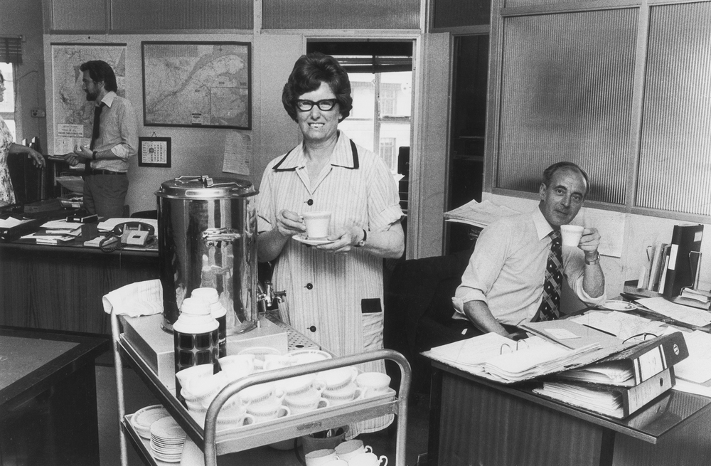 A tea lady brings round refreshments for British office workers in the 1970s. All over the U.K., the arrival of the tea ladies with trolleys loaded with a steaming tea urn and a tray of cakes or buns was the high point of the workday.