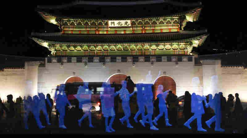"""Holograms of human figures are displayed during a """"ghost protest"""" against South Korea's president in front of the Gyeongbok Palace in Seoul on Wednesday. Amnesty International in Korea said it decided to use the holograms after protesters were denied permission to march. See the video below."""