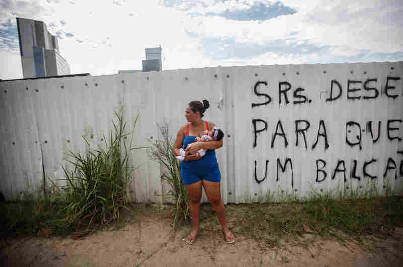Resident Rafaela Silva dos Santos holds her baby Sofia Valentina as she watches an argument between police and residents nearby, in the mostly demolished Vila Autodromo favela community, on February 24, 2016 in Rio de Janeiro, Brazil. Dos Santos said she fears her baby will contract the Zika virus as another member of the community was diagnosed with Zika two weeks ago.