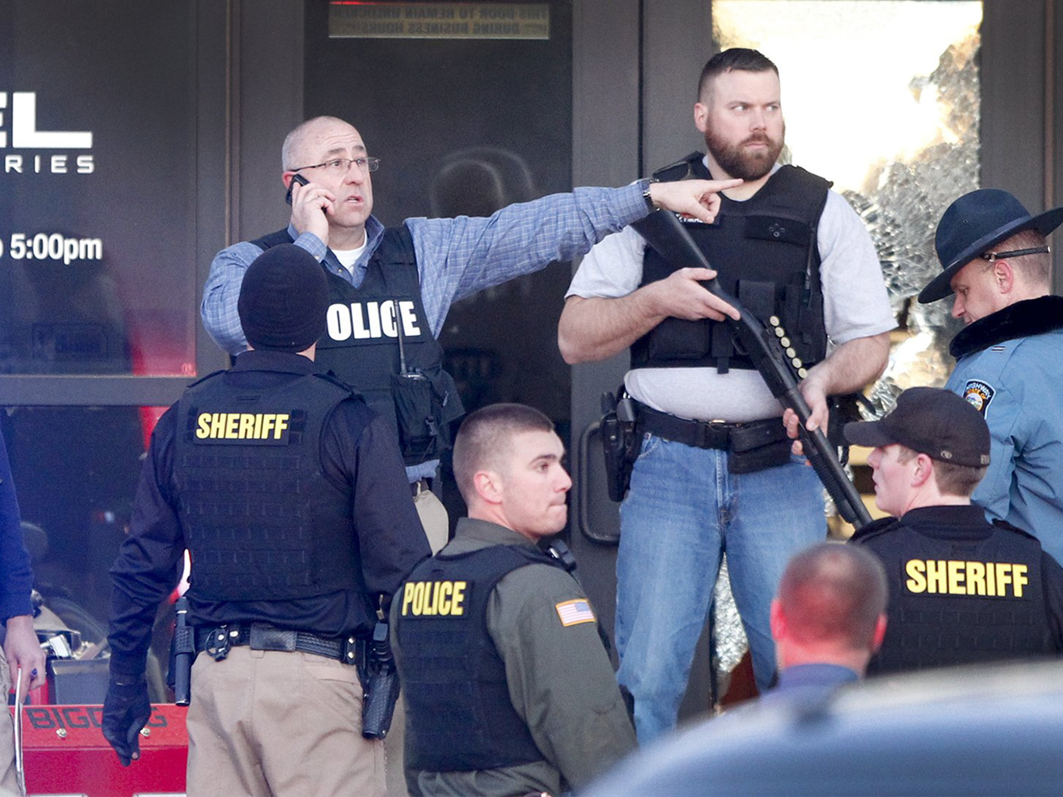 Police guard the front door of Excel Industries in Hesston, Kan., where a gunman reportedly killed three people before being shot to death by a police officer.