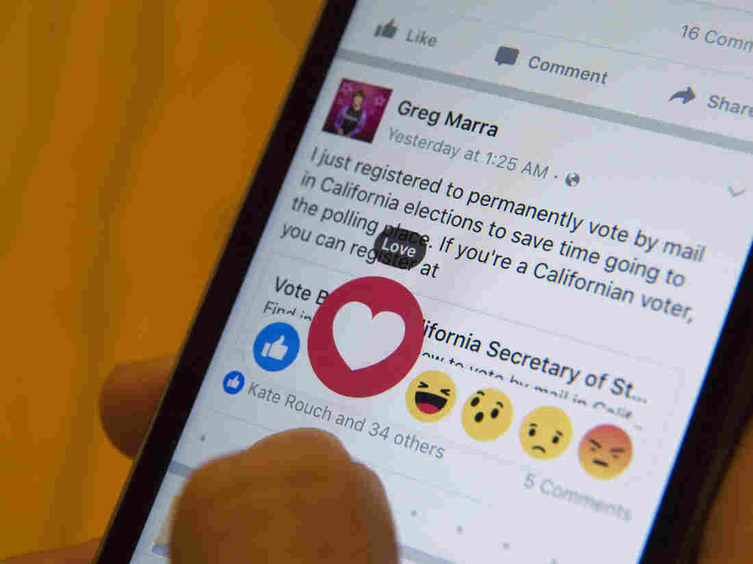 Julie Zhuo, product design director at Facebook, demonstrates the new emoji-like stickers users can press in addition to the like button.
