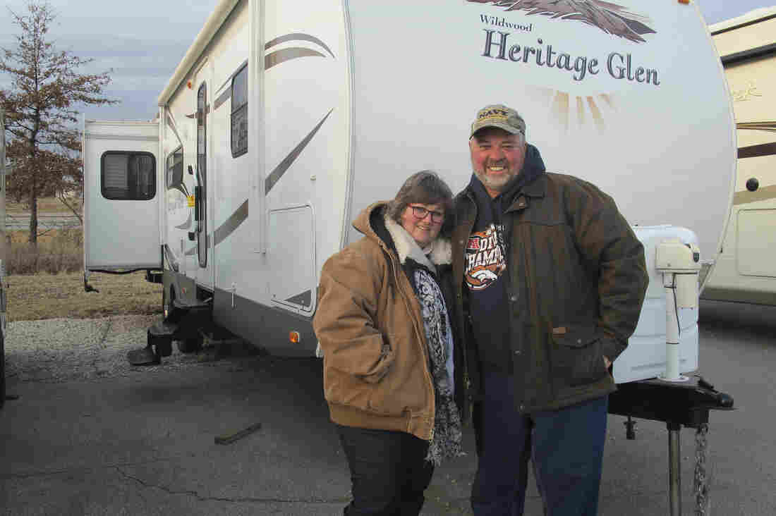 Grant and Cathy Lowe stand in front of a trailer they just bought. It is part of their retirement plans to own this camper, and they intend to have it paid off before they quit working.