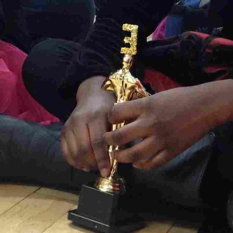 A student holds her Academy Award of Excellence statue.