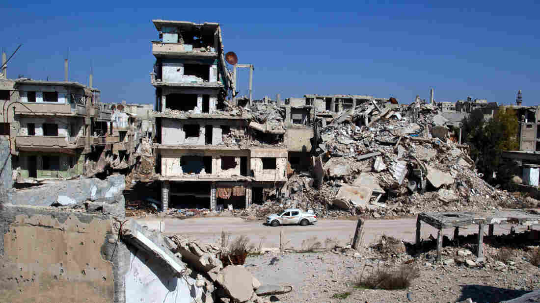 A car drives through a devastated part of the old city of Homs, Syria, on Friday.