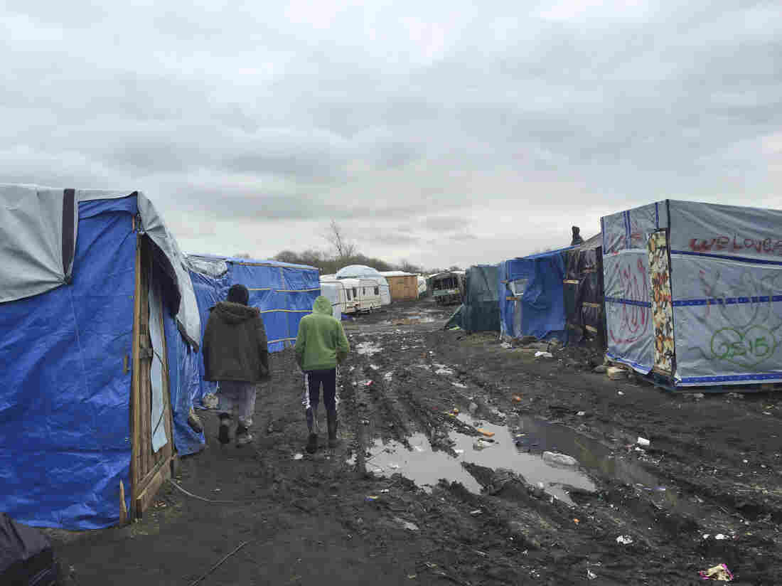 "Amran, an unaccompanied minor from Afghanistan, at right, walks in the camp known as the Jungle with 35-year-old Farid Hamdan, a father of four, also from Afghanistan. ""My heart is saying help him because he's only a kid,"" says Hamdan. ""He has nobody else here to look after him."" There are 300 to 400 children staying in the Jungle."