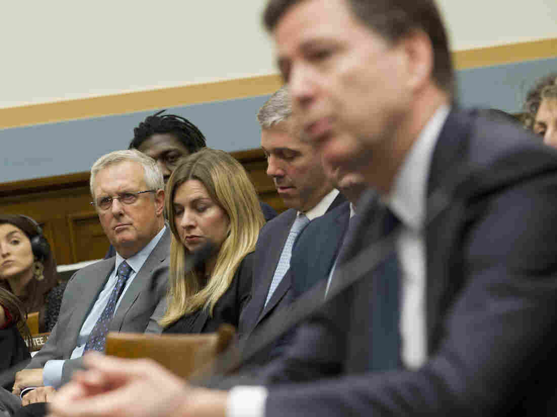 Apple General Counsel Bruce Sewell (left) listens to FBI Director James Comey testify before the House Judiciary Committee on Tuesday.