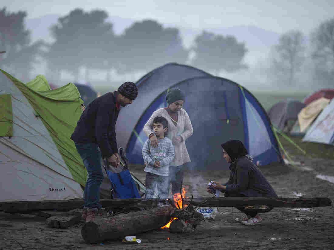 A family warms by a fire in the early morning on the Greek-Macedonia border on Tuesday in Idomeni, Greece.