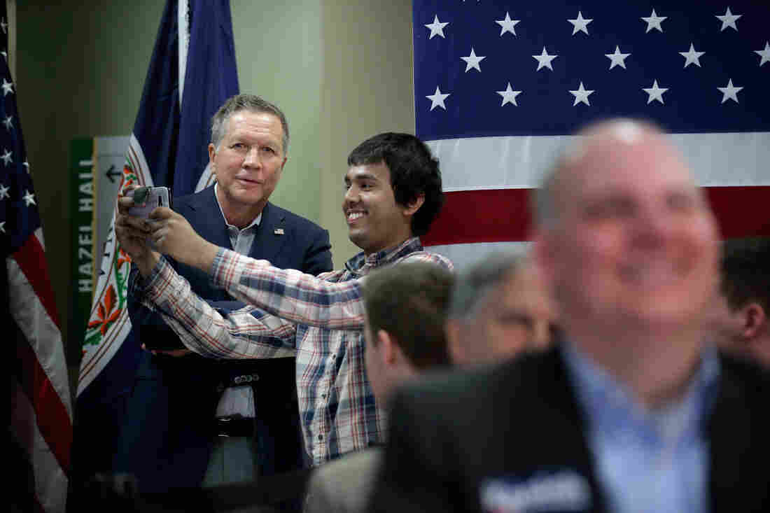 A student jumps up from the audience to take a selfie with Republican presidential candidate John Kasich during a town hall-style meeting at George Mason University Law School in Fairfax, Va.