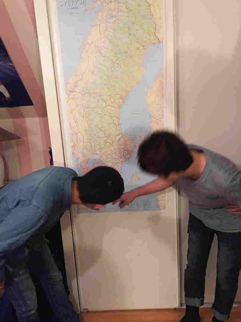 Navid, 14, and Mohsen, 15, who traveled from Afghanistan to Sweden last year without their families, examine a map of Sweden hanging in their new home.