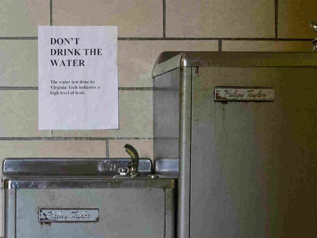 Signs warn not to drink the lead-contaminated water from a water fountain in Flint, Mich.