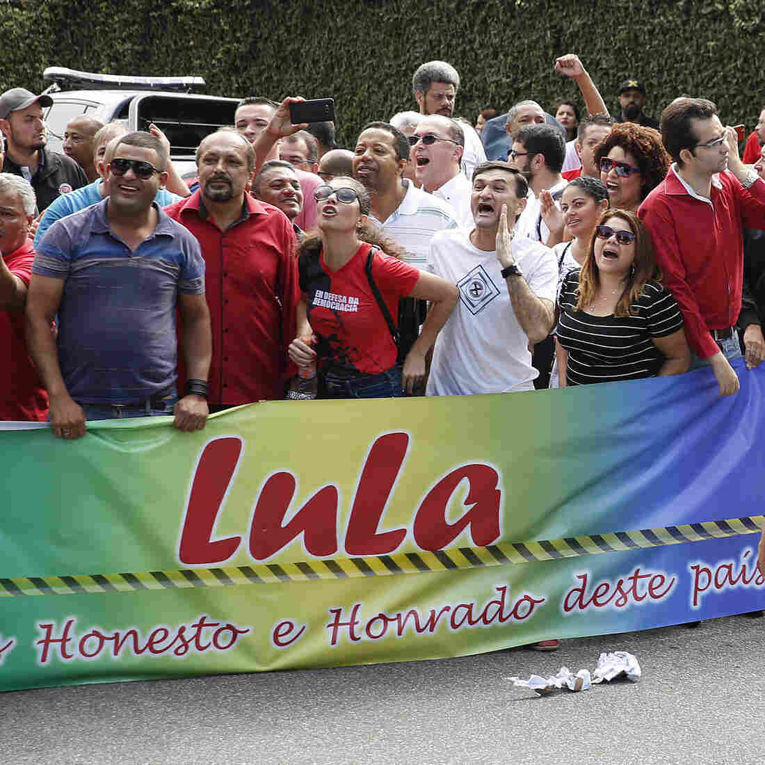 Demonstrators shout in support of Brazil's former President Luiz Inacio Lula da Silva outside his residence in the greater Sao Paulo area Friday. Police searched Silva's home and are questioning the former leader in relation to a corruption and money-laundering case.