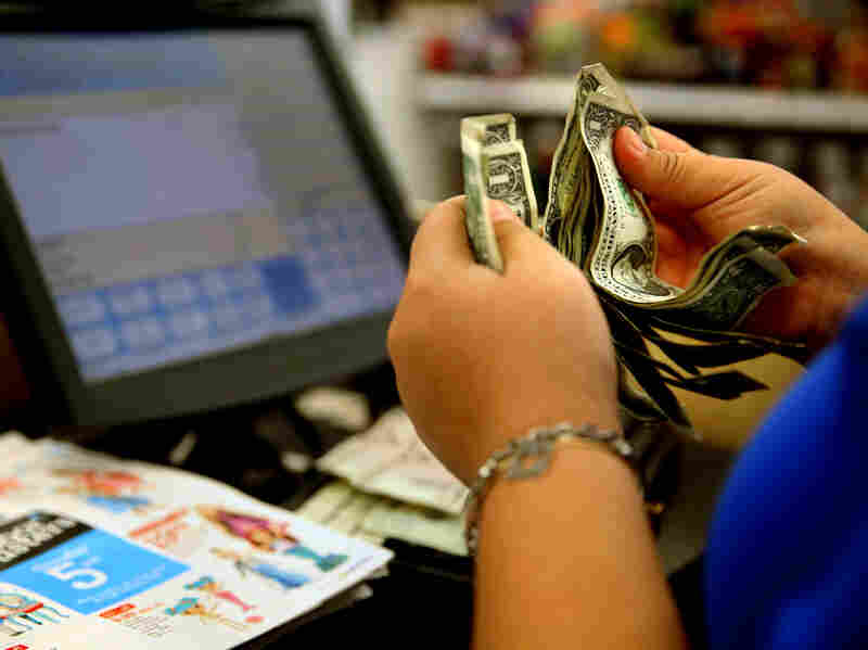 """A cashier counts money at a Toys """"R"""" Us in Los Angeles last November. A pinch in earnings and hours disappointed those looking for a pickup in paychecks last month."""