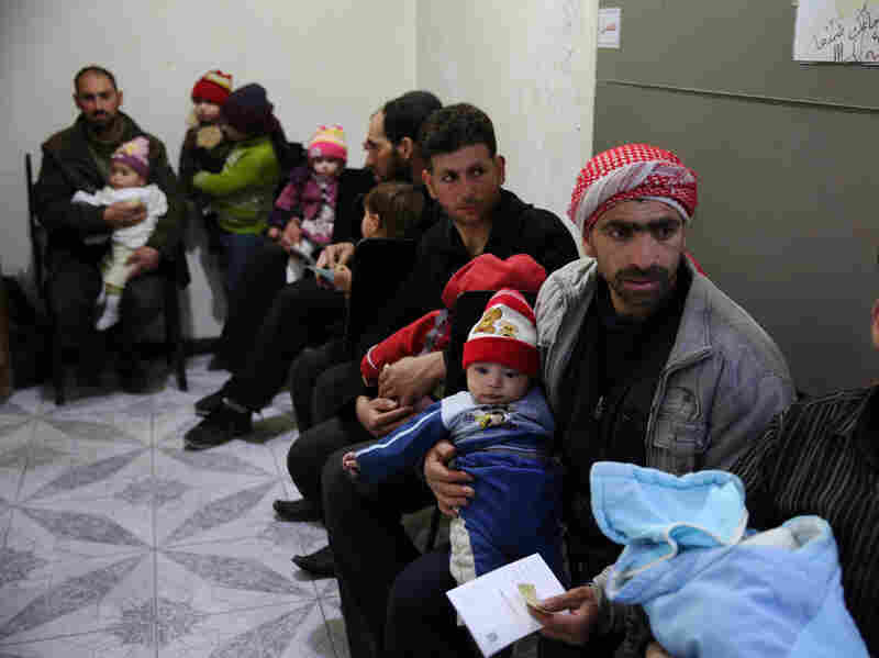 Syrian men and children wait to receive vaccinations at the Syrian Arab Red Crescent center in the rebel-held town of Douma, on the eastern edges of Damascus, on Thursday. The vaccines were part of the first batch of aid delivered to areas in need of assistance since the start of Syria's cease-fire.